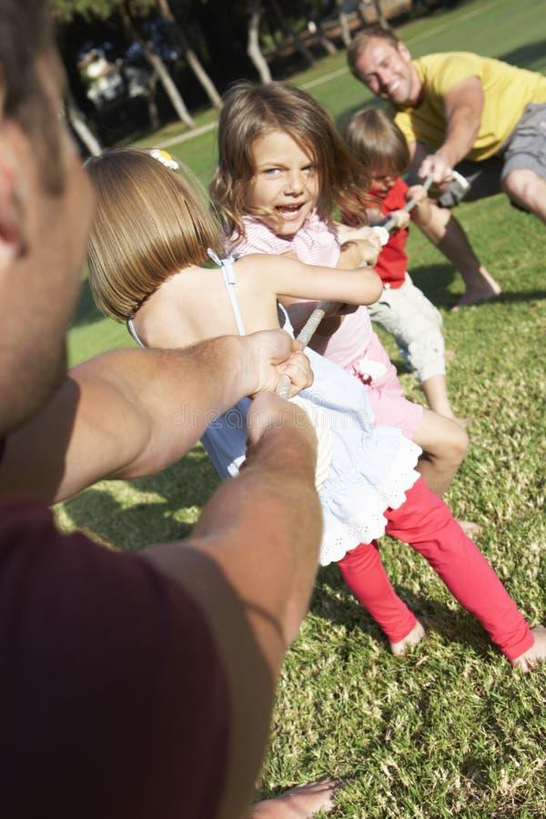 Fäder och barn som spelar dragkampen arkivbild