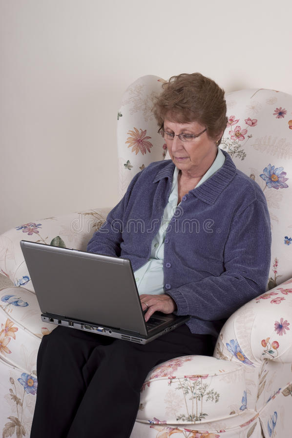Fällige ältere Frauen-Laptop-Computer, ernster Blick stockfotografie