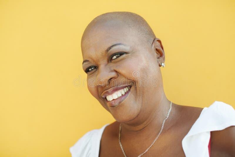 Fällige afrikanische Frau, die an der Kamera lächelt lizenzfreie stockbilder