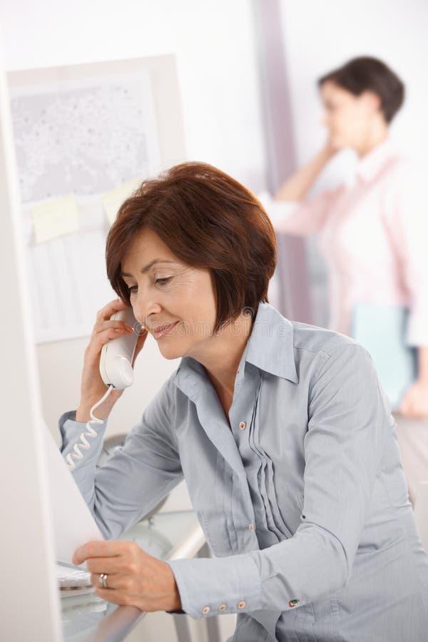 Fällige Büroangestelltfrau, die Überlandleitungtelefon verwendet stockfotos