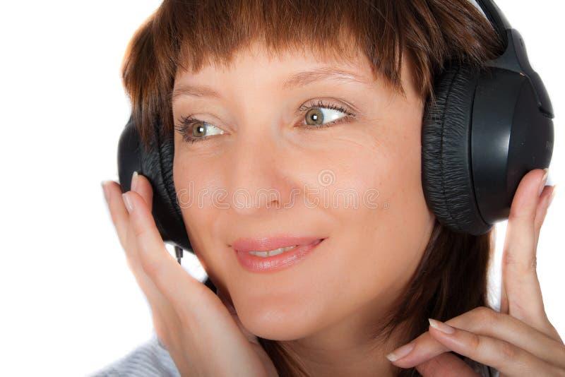 Fällige Frau in den Kopfhörern stockfoto