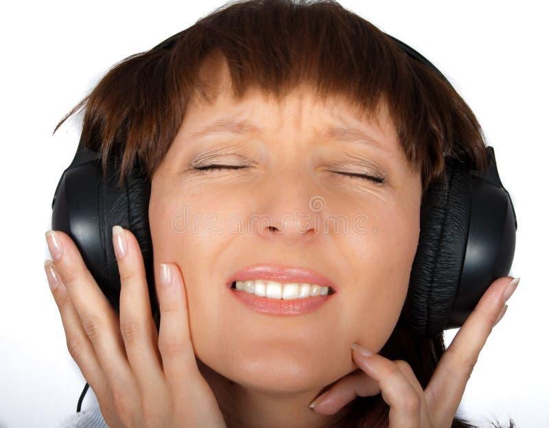 Fällige Frau in den Kopfhörern stockbild