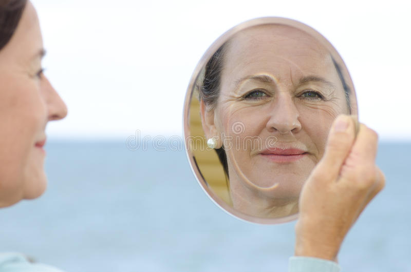 Fällige Frau des Portraits im Spiegel lizenzfreies stockfoto