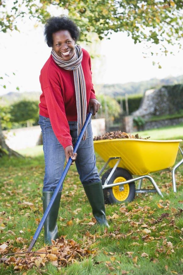 Fällige Frau, die Blätter im Garten montiert lizenzfreie stockfotos