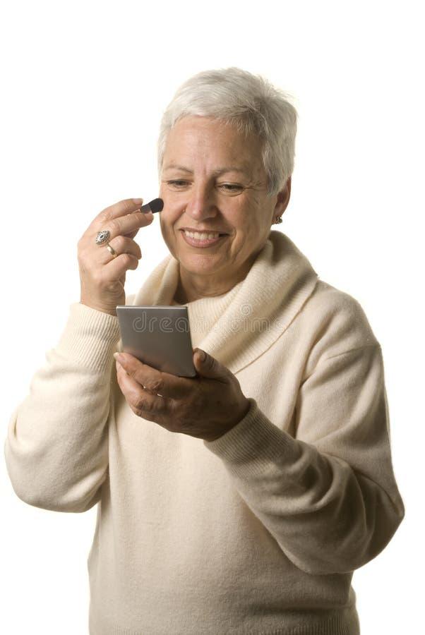 Fällige Frau, die Blusher anwendet lizenzfreie stockfotografie