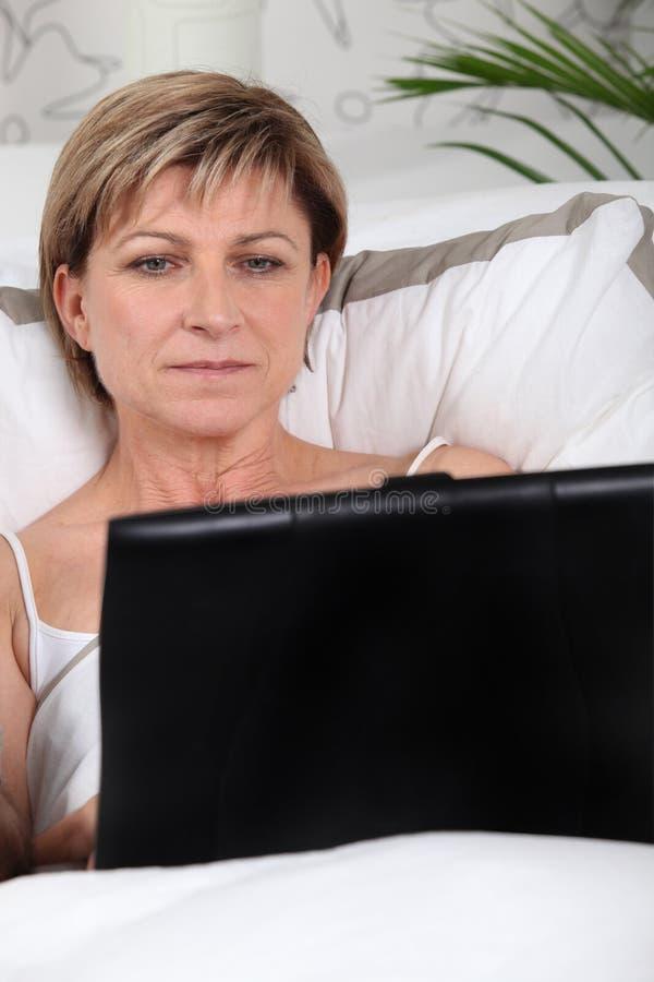 Fällige Frau, die einen Laptop verwendet stockfoto