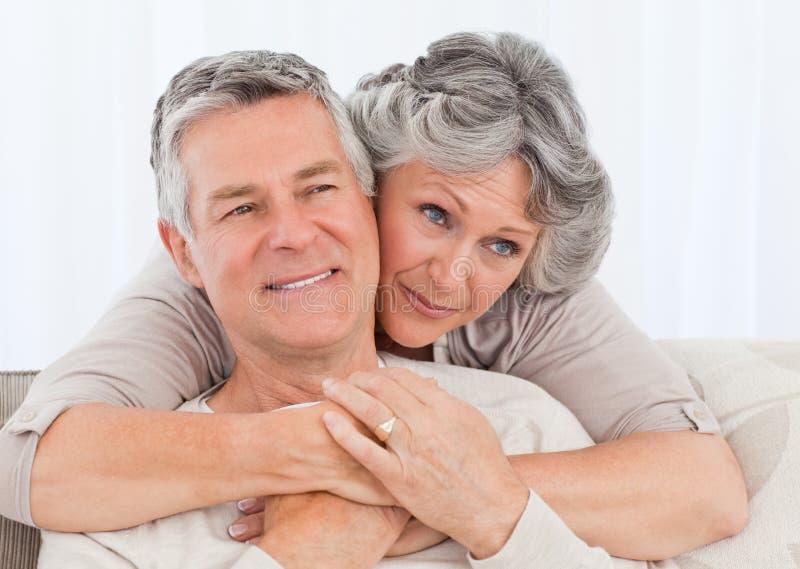 Fällige Frau, die ihren Ehemann umarmt stockbild