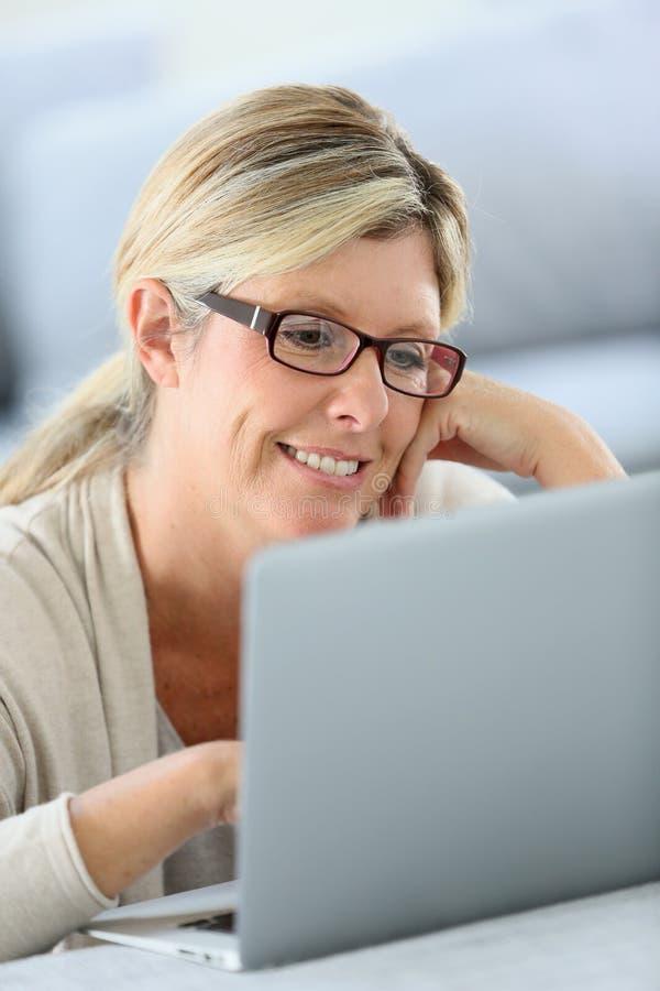 Fällige Frau, die an Laptop arbeitet lizenzfreies stockfoto