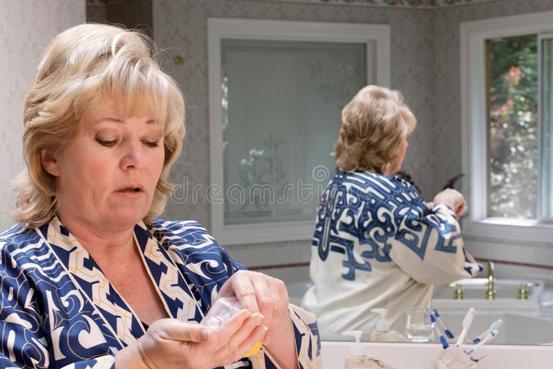 Fällige Frau, die Pillen zählt, um zu nehmen stockbild