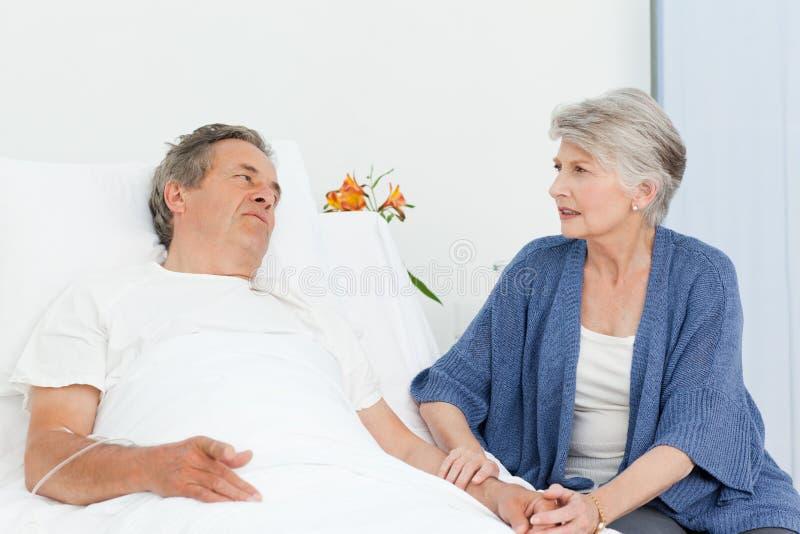 Fällige Frau, die um ihrem Ehemann sich kümmert stockfoto