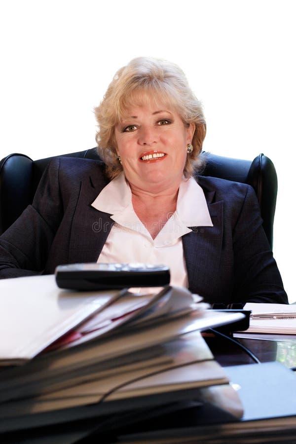 Fällige Frau lächelt an ihrem Schreibtisch stockfotografie