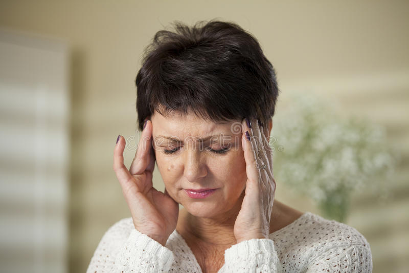 Fällige Frau mit Kopfschmerzen stockfotos