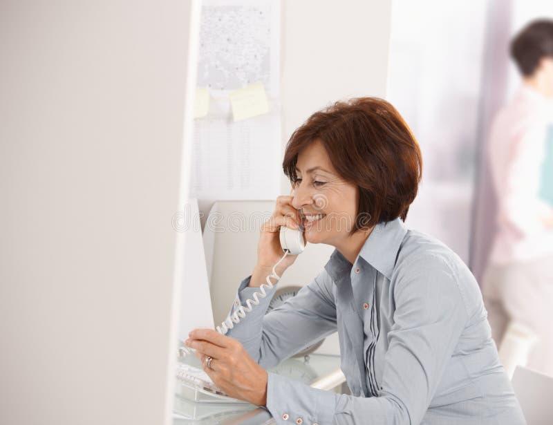 Fällige Geschäftsfrau, die am Überlandleitungtelefon spricht lizenzfreie stockfotografie