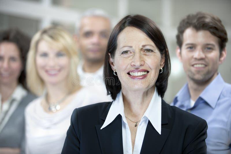 Fällige Geschäftsfrau und Geschäftsteam stockbilder