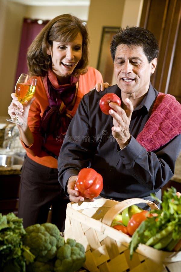 Fällige Paare in der Küche mit Frischgemüse stockfotografie