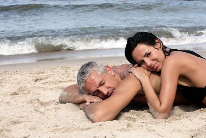 Fällige Paare, die auf dem Strand sich entspannen lizenzfreies stockfoto