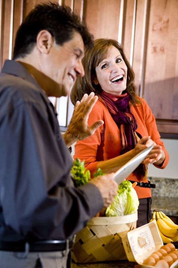 Fällige Paare, die Spaß haben zu kochen in der Küche lizenzfreie stockfotografie