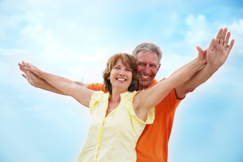 Fällige Paare mit den Armen ausgestreckt stockbild