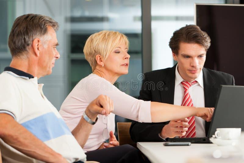 Fällige Paare mit Finanzberater stockfotos