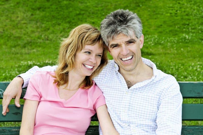 Fällige romantische Paare auf einer Bank stockfotografie