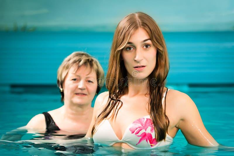 Fällige und junge Frau des Wellness - im Swimmingpool lizenzfreie stockfotos