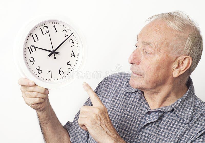 Fälliger älterer Mann, der Borduhr betrachtet. lizenzfreies stockbild
