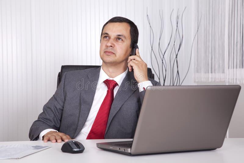 Fälliger Geschäftsmann, der im Büro arbeitet lizenzfreie stockbilder