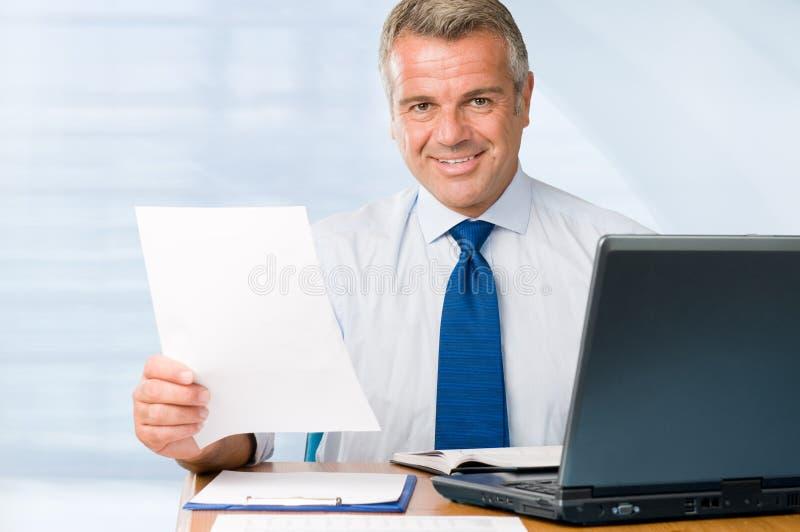 Fälliger Geschäftsmann, der im Büro arbeitet stockbild