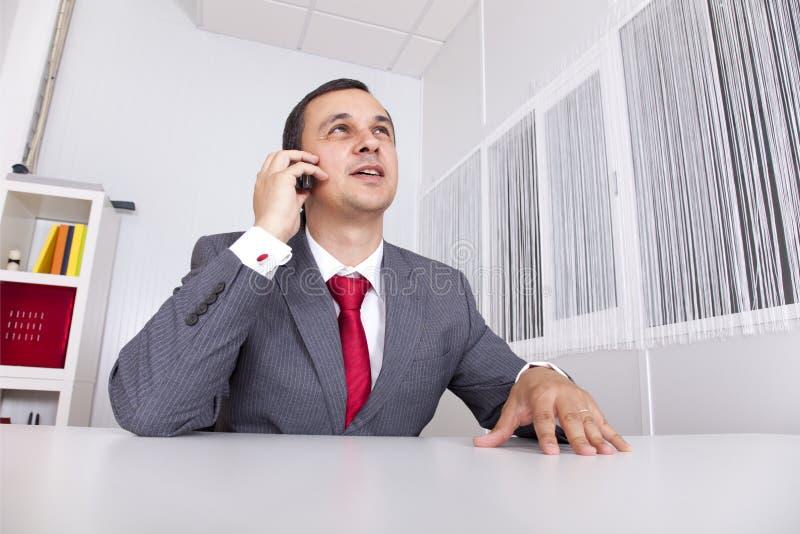 Fälliger Geschäftsmann, der im Büro arbeitet lizenzfreies stockbild
