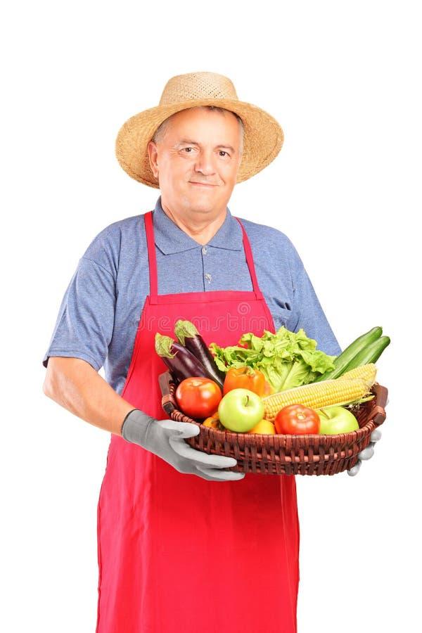 Fälliger Landwirtmann, der einen Korb anhält lizenzfreies stockfoto