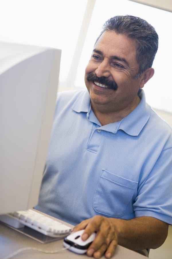 Fälliger männlicher Kursteilnehmer, der Computerfähigkeiten erlernt lizenzfreie stockfotos