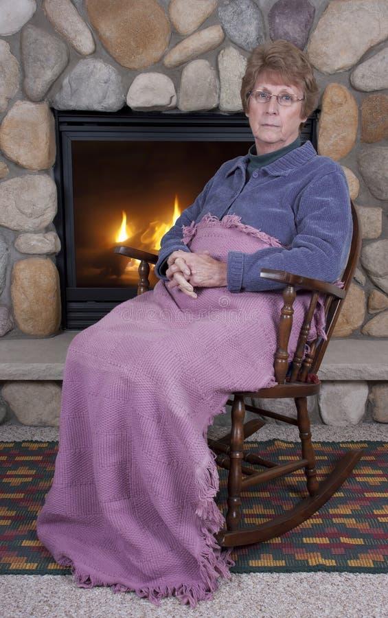 Fälliges älteres Frauen-trauriges Gesichts-Schwingstuhl, Feuer lizenzfreie stockfotos