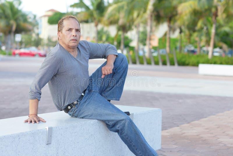 Fälliges erwachsenes Sitzen auf einer Parkbank stockfoto
