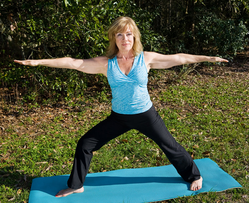 Fälliges Frauen-Yoga - Krieger-Haltung stockfotografie