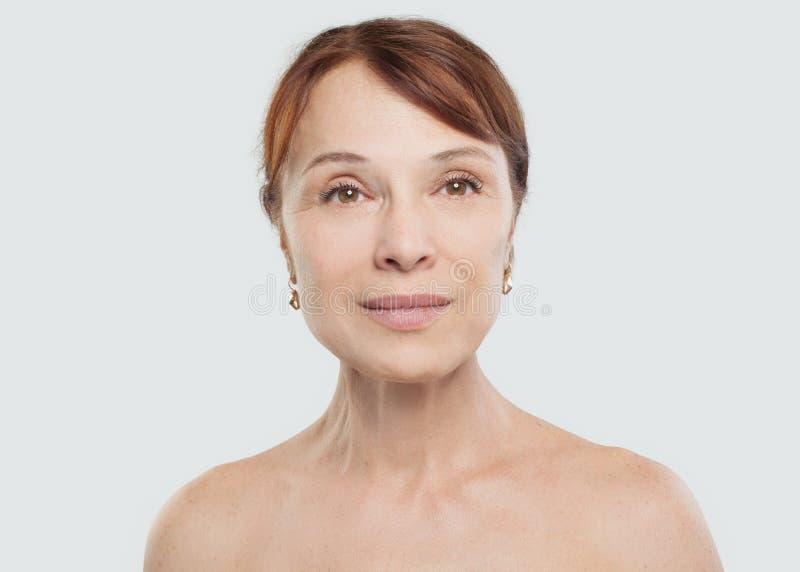 Fälliges Frauenlächeln Schönes mittleres erwachsenes weibliches Gesicht lizenzfreie stockbilder