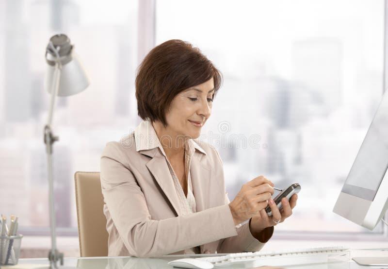 Fälliges weibliches Leitprogramm, das smartphone im Büro verwendet stockbild
