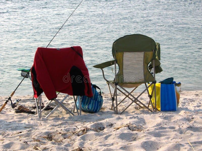 Fällstolar och fiske på stranden royaltyfri foto