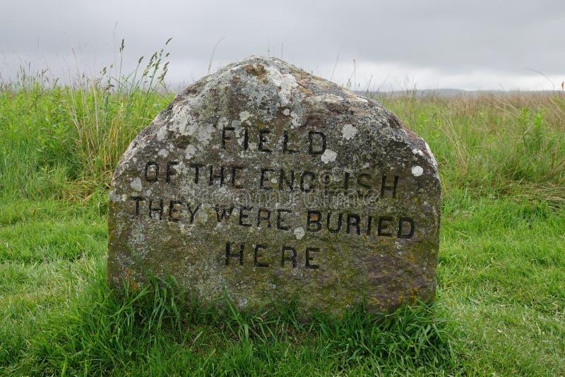 FÄLT AV ENGELSKAET - DE VAR DEN BEGRAVDE HÄR massgravmarkören på den Culloden slagfältet, Skottland royaltyfri bild