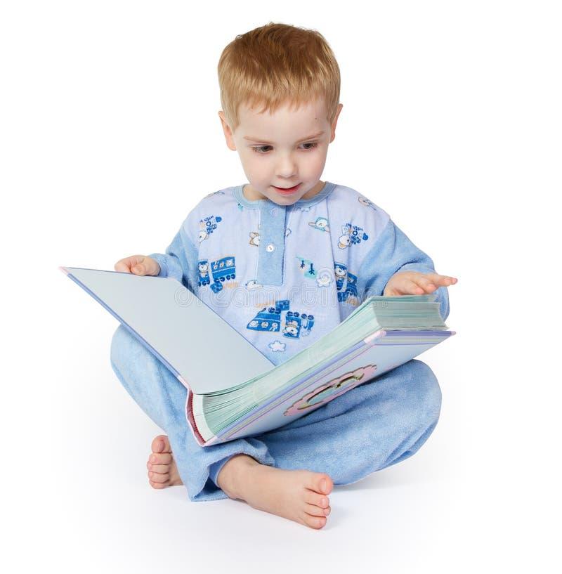 fält för djup för bokkamerabarn som ser grund avläsning Kin Sitting i blå Nightwear och läsning, isolerad vit royaltyfria foton