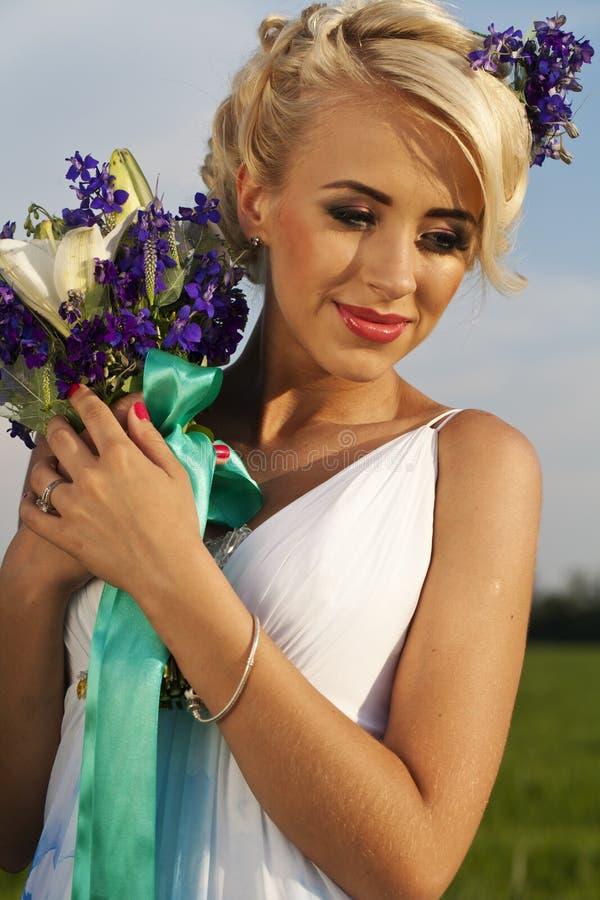 Fält för gräsplan för blåa ögon för härlig brud blont royaltyfri foto