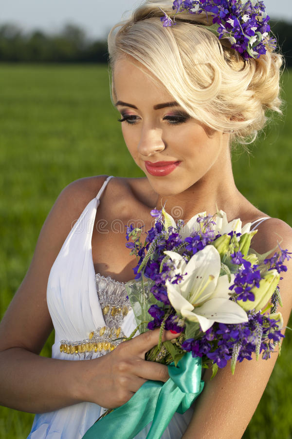 Fält för gräsplan för blåa ögon för härlig brud blont royaltyfria foton
