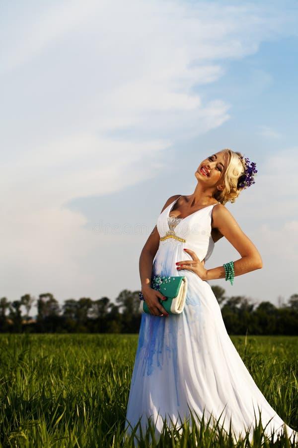 Fält för gräsplan för blåa ögon för härlig brud blont royaltyfri bild