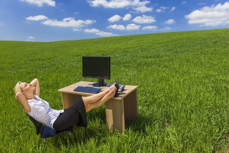 Fält för gräsplan för skrivbord för kontor för affärskvinna avslappnande royaltyfri foto