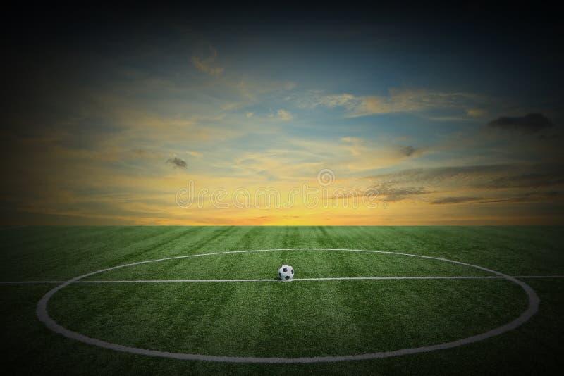 Fält för grönt gräs för fotboll på solnedgången royaltyfri fotografi