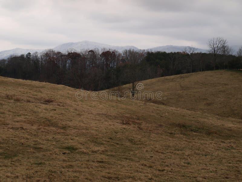 Fält och berg i vinter arkivbild
