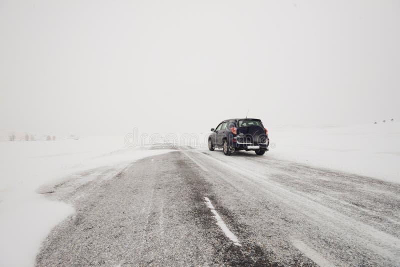 Fält och en väg i vinter och en bil arkivfoton