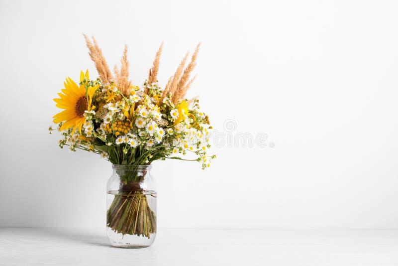 Fältblommor i en exponeringsglasvas Sommarbukett av blommor på den vita bakgrunden royaltyfri fotografi
