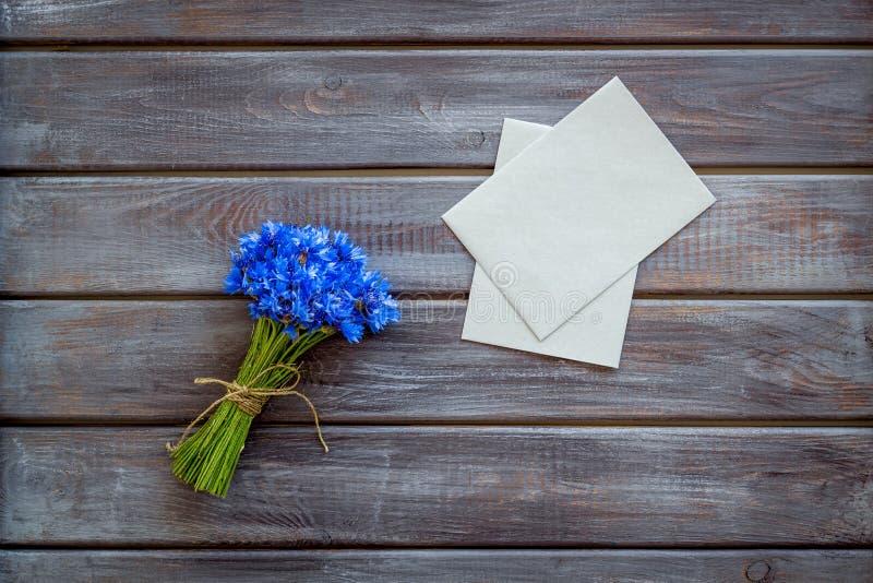 Fältblommor planlägger med buketten av blåa blåklinter och kuvert för gåva på trämodell för bästa sikt för bakgrund royaltyfri foto