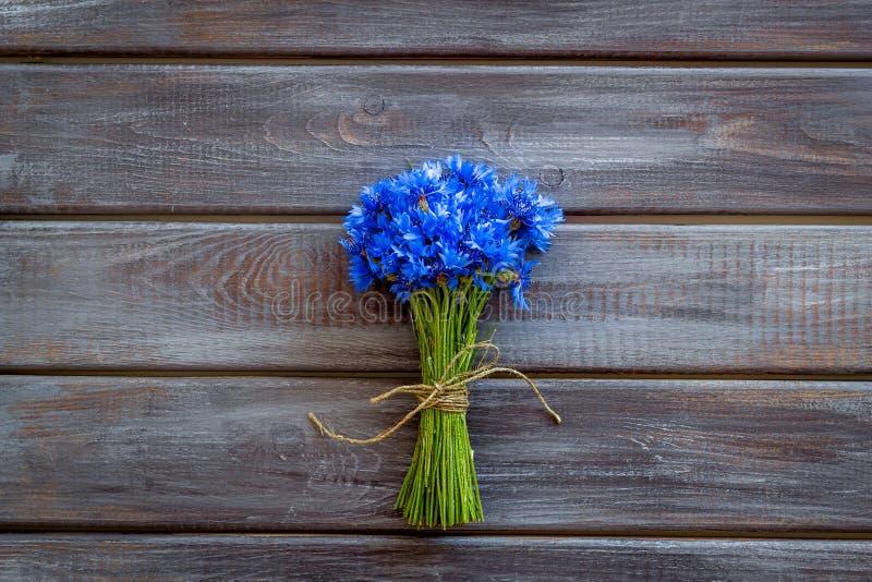 Fältblommor planlägger med buketten av blåa blåklinter på träutrymme för den bästa sikten för bakgrund för text royaltyfri foto