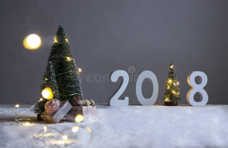Fältet under gran-träden, hunden sover på gåvor och i avstånd är diagram 2018 var i rollen av en julgran arkivbilder